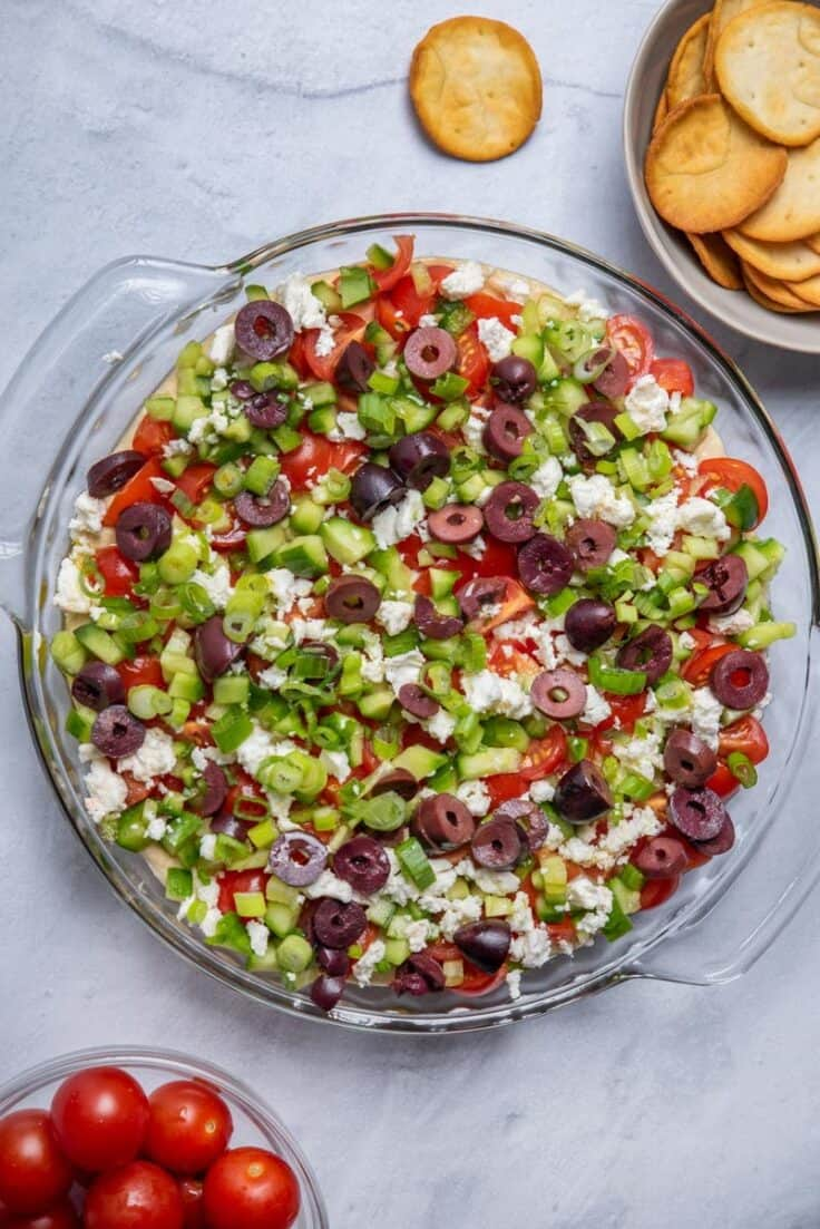 7 layer mediterranean dip with pita chips served on the side