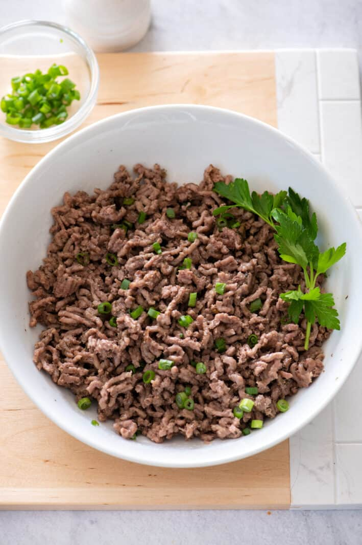 Cooked ground beef from instant pot in bowl with parsley