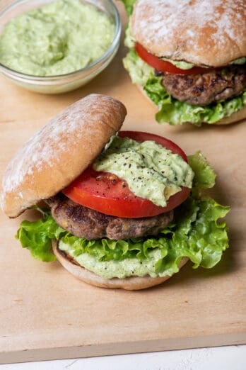Two avocado burgers with avocado crema on the side