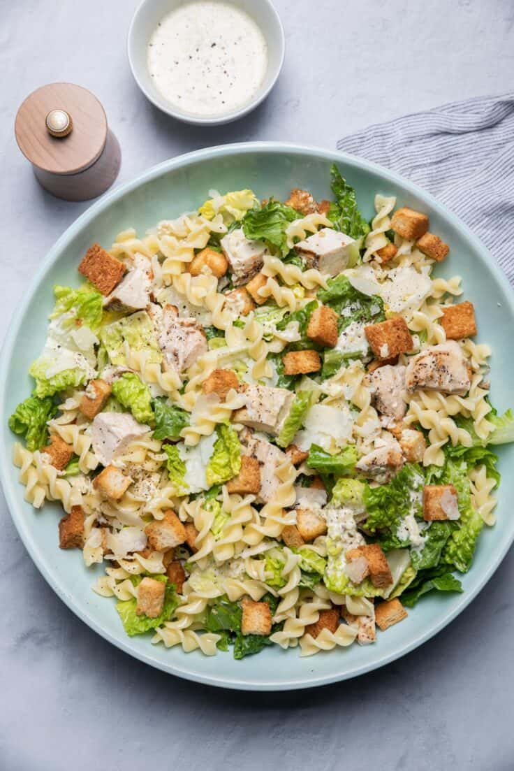 Chicken Caesar pasta salad in a large bowl with homemade croutons