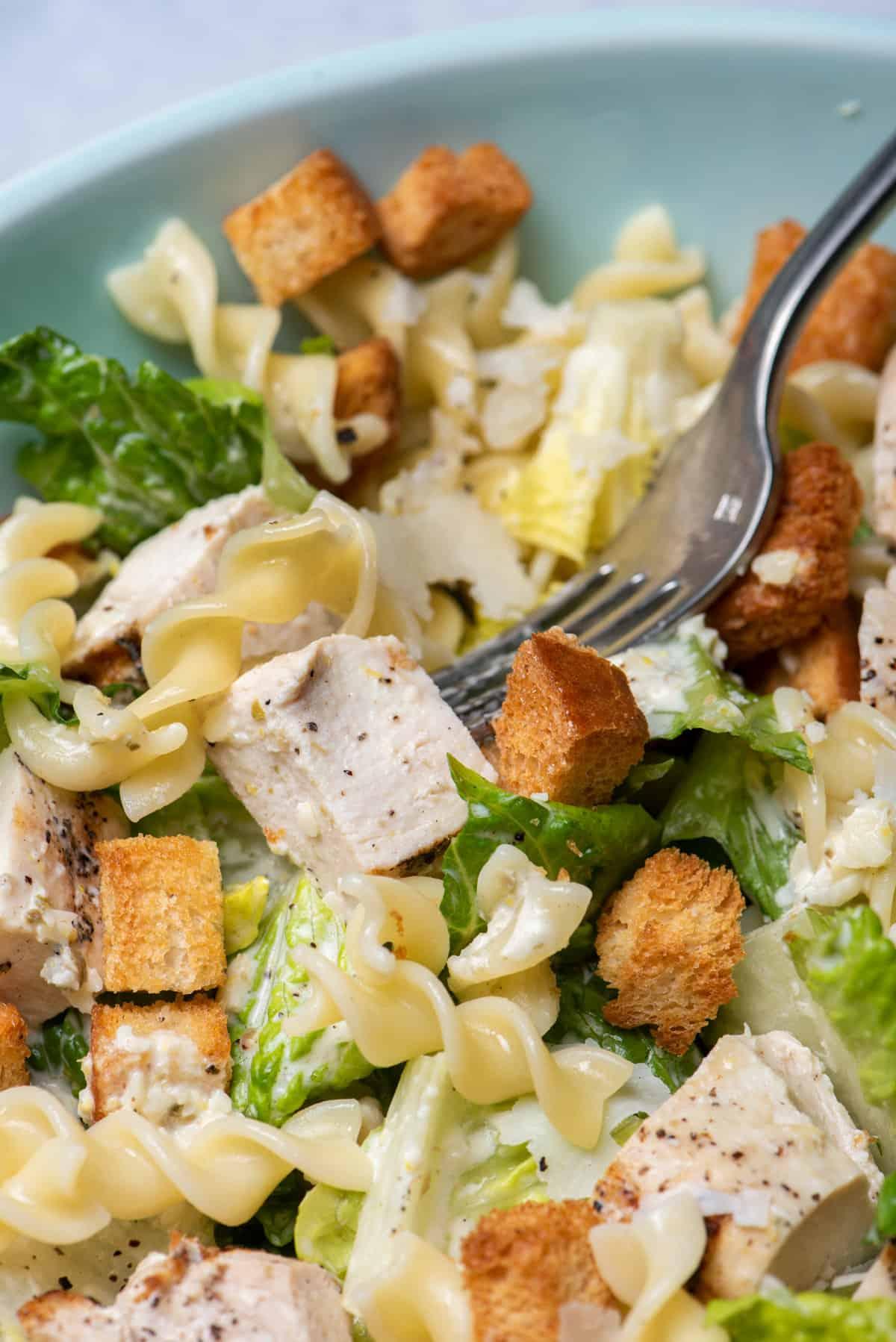 Bite taking bite of chicken caesar pasta salad