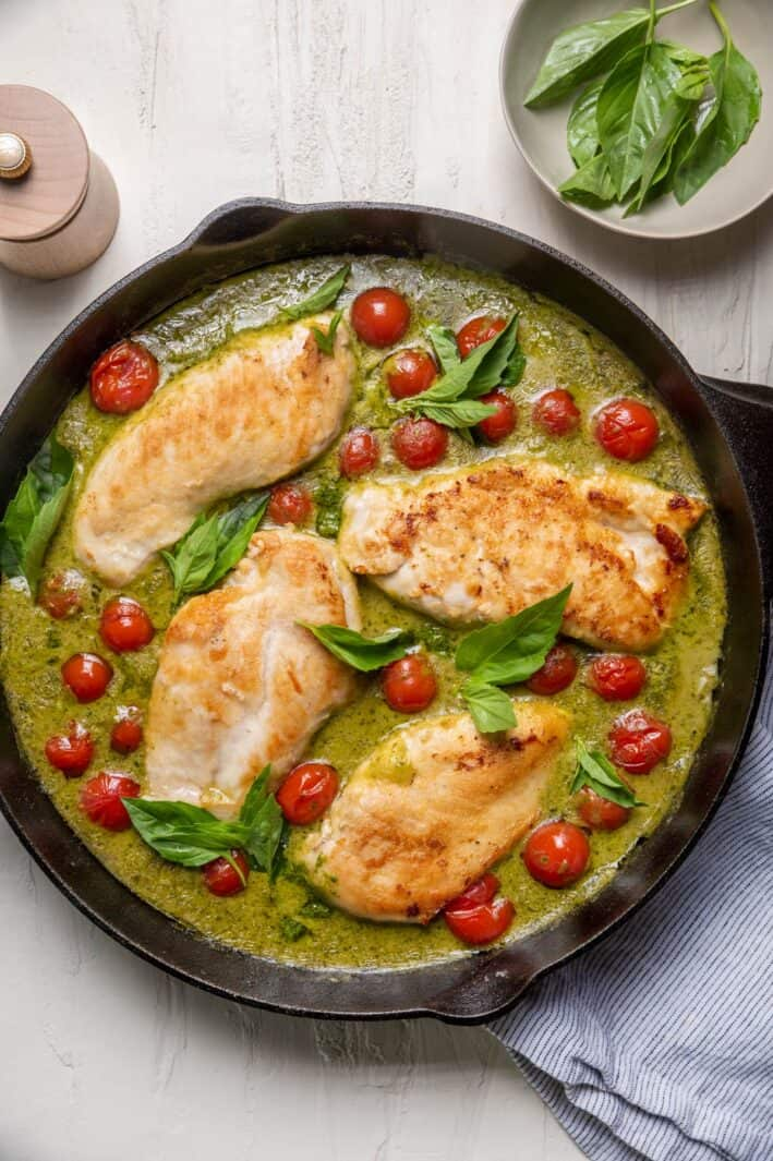 Creamy pesto chicken in a skillet with cherry tomatoes