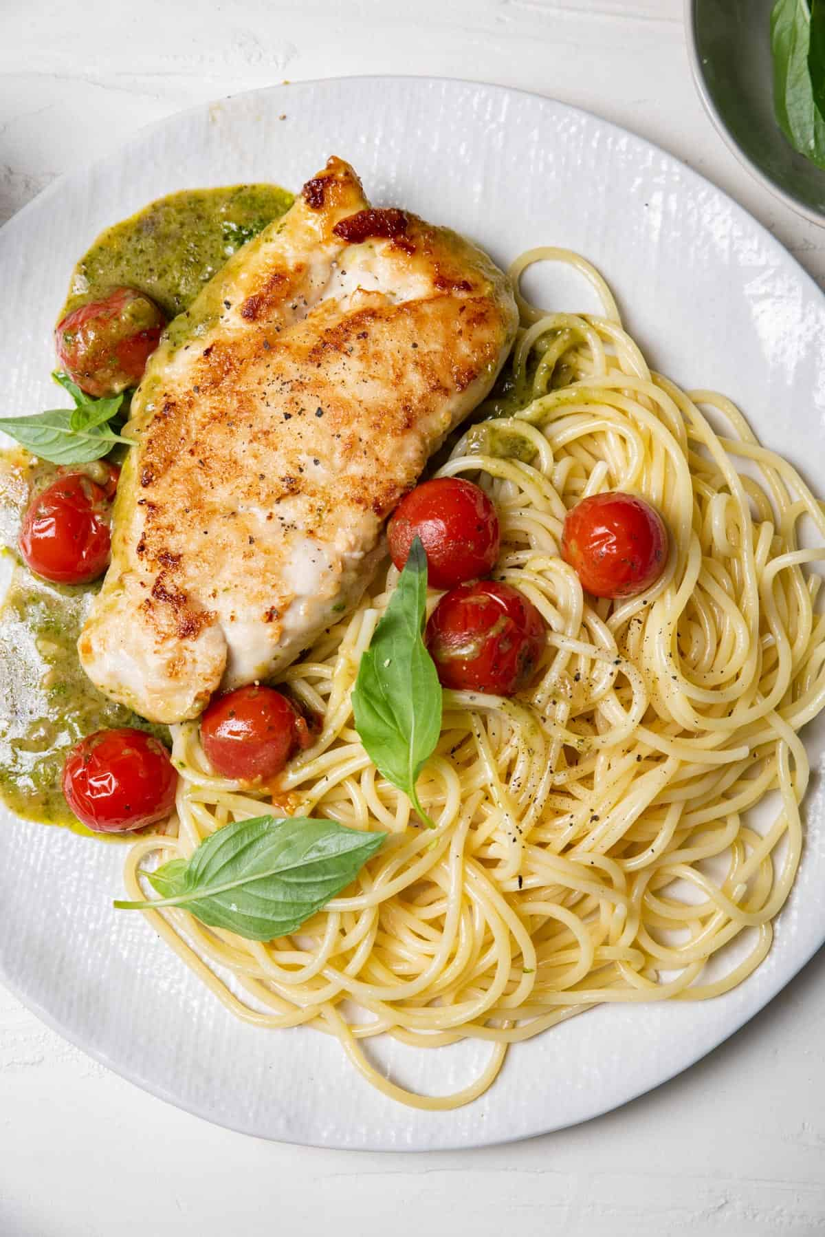 Creamy pesto chicken served with spaghetti and cherry tomatoes