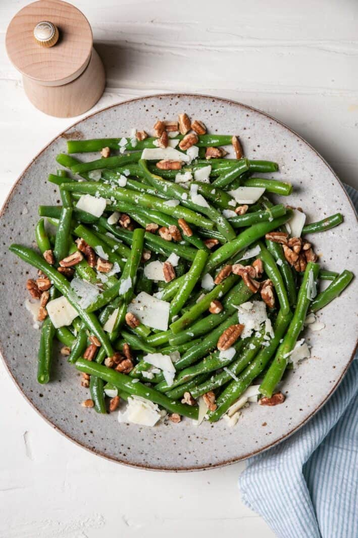 Bowl of green bean salad with honey dijon dressing and parmesan cheese