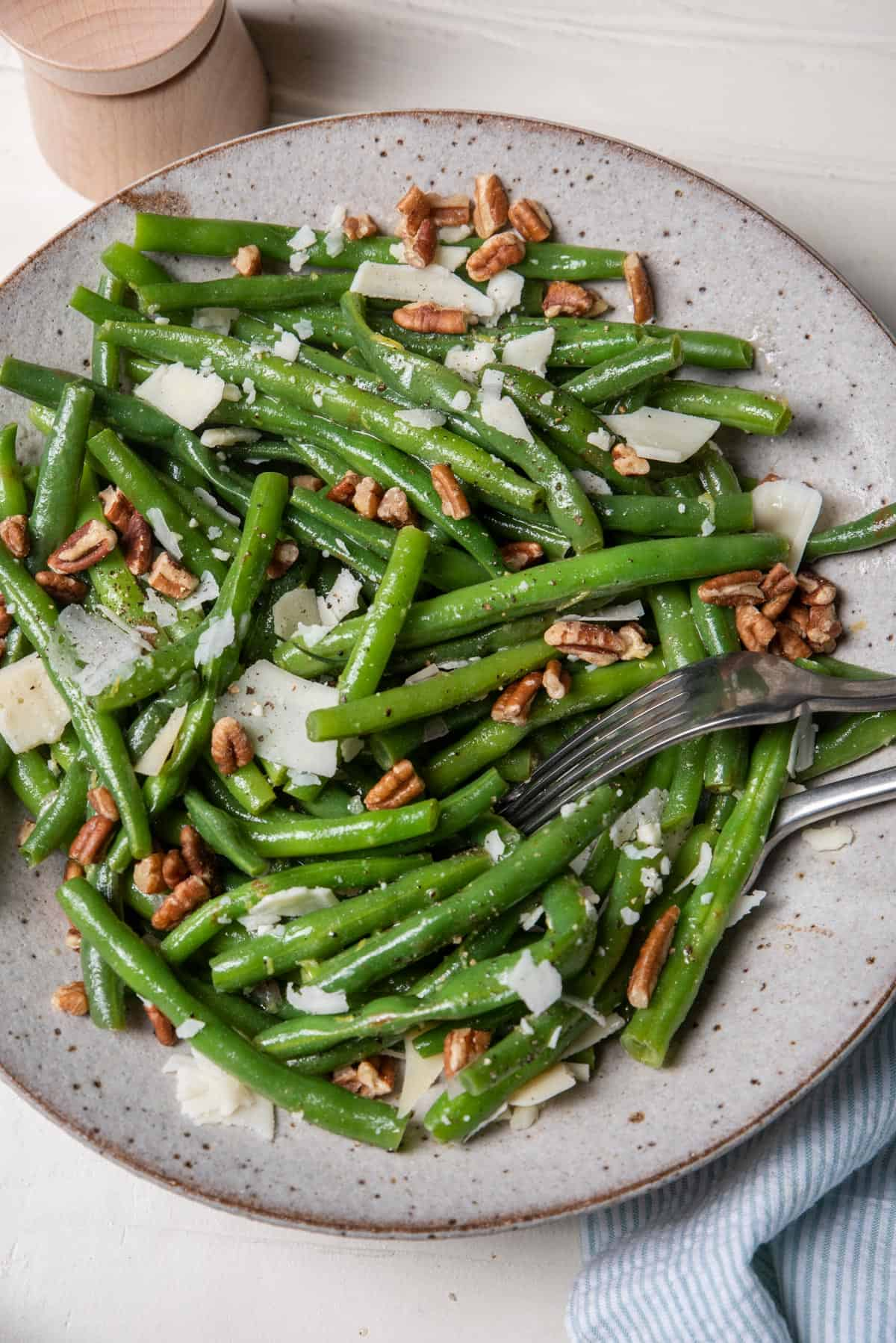 Large bowl of green bean salad with parmesan cheese and pecans
