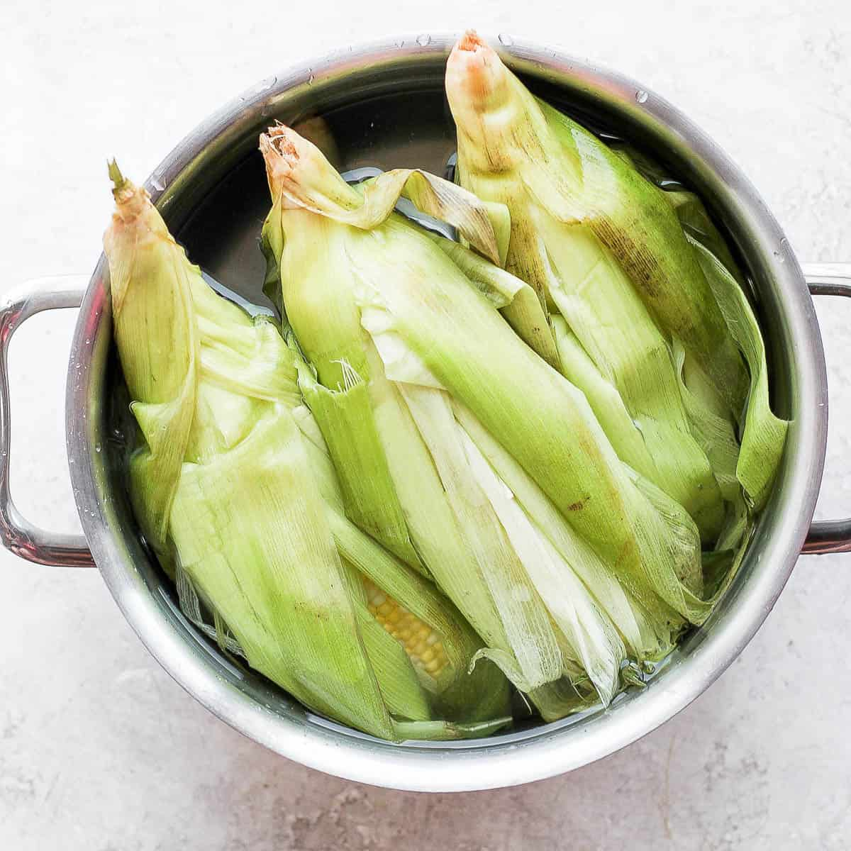 Corn with husks getting soaked in pot of water