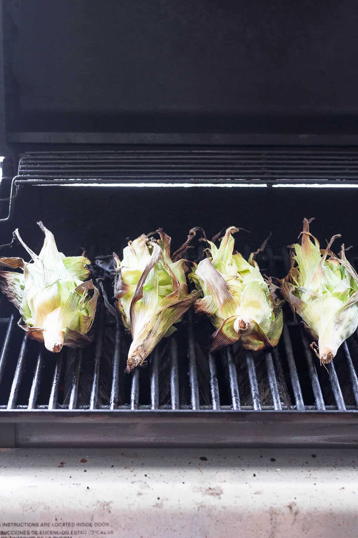 4 corns with husks on grill