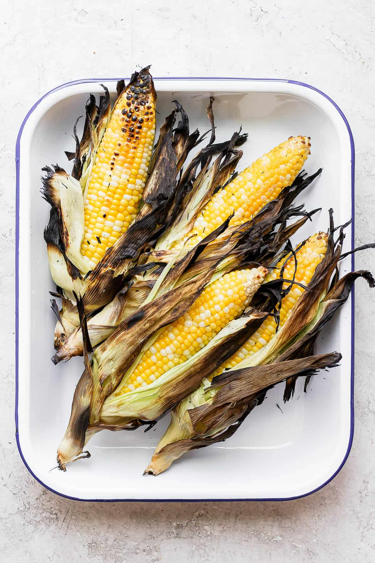 Pan of grilled corn with husks