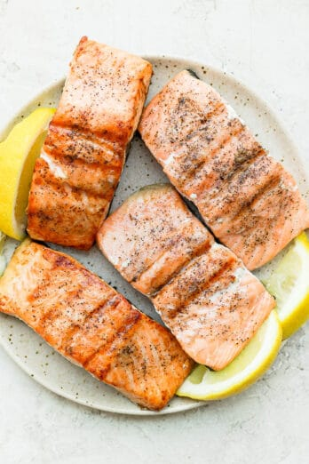Plate of 4 salmon fillets grilled served with lemon wedges
