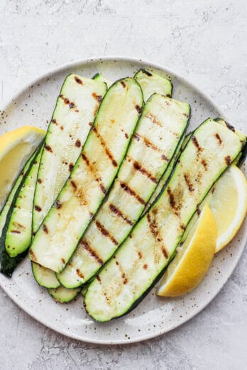 Grilled zucchini slices on a plate with lemon wedges