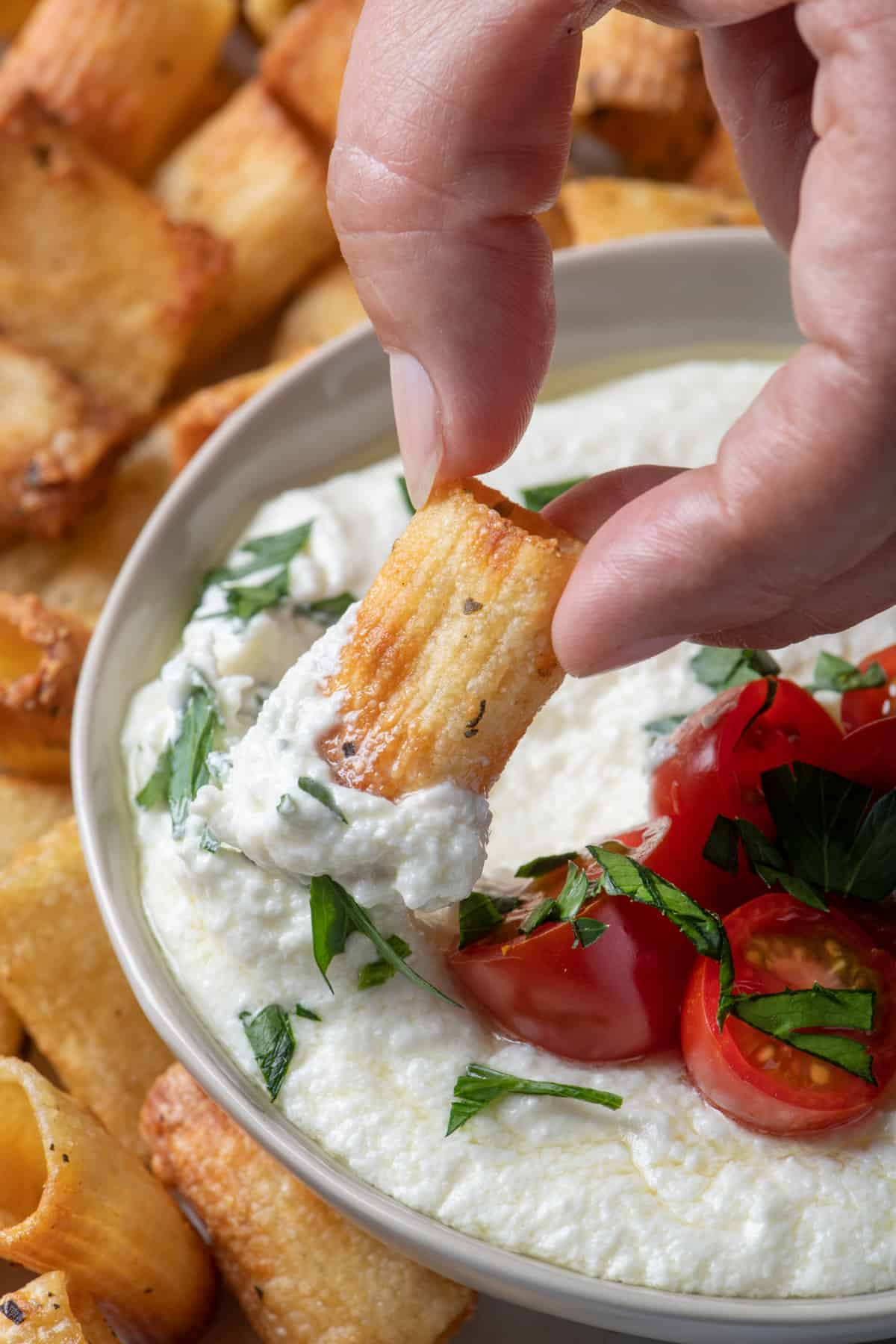 Pasta chip dipping into whipped feta dip