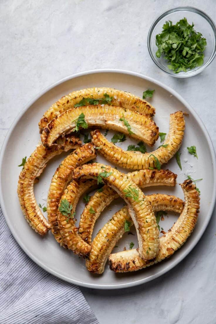 Plate of corn ribs served with side of cilantro