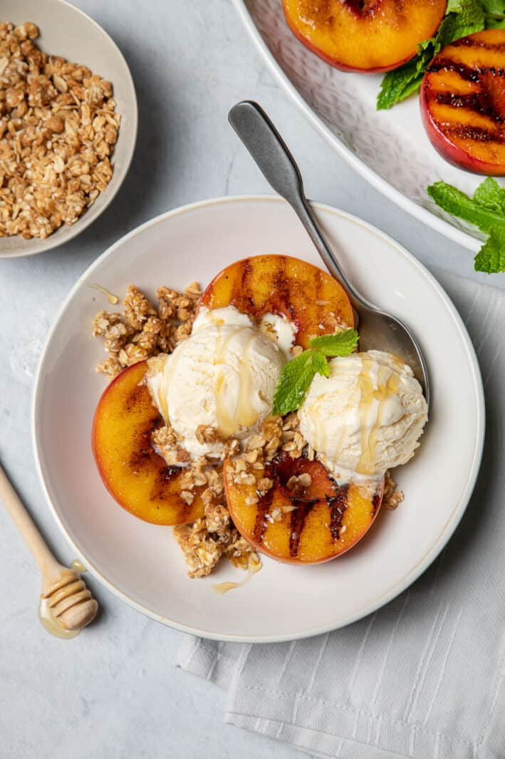 3 grilled peach halves in a bowl topped with ice cream, granola and fresh mint