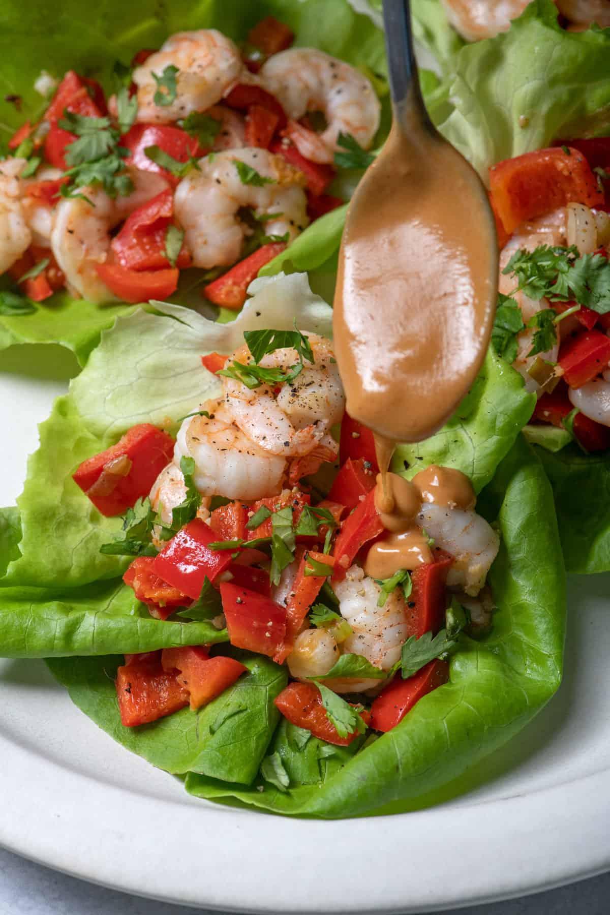 Spoon drizzling peanut sauce over shrimp lettuce wraps