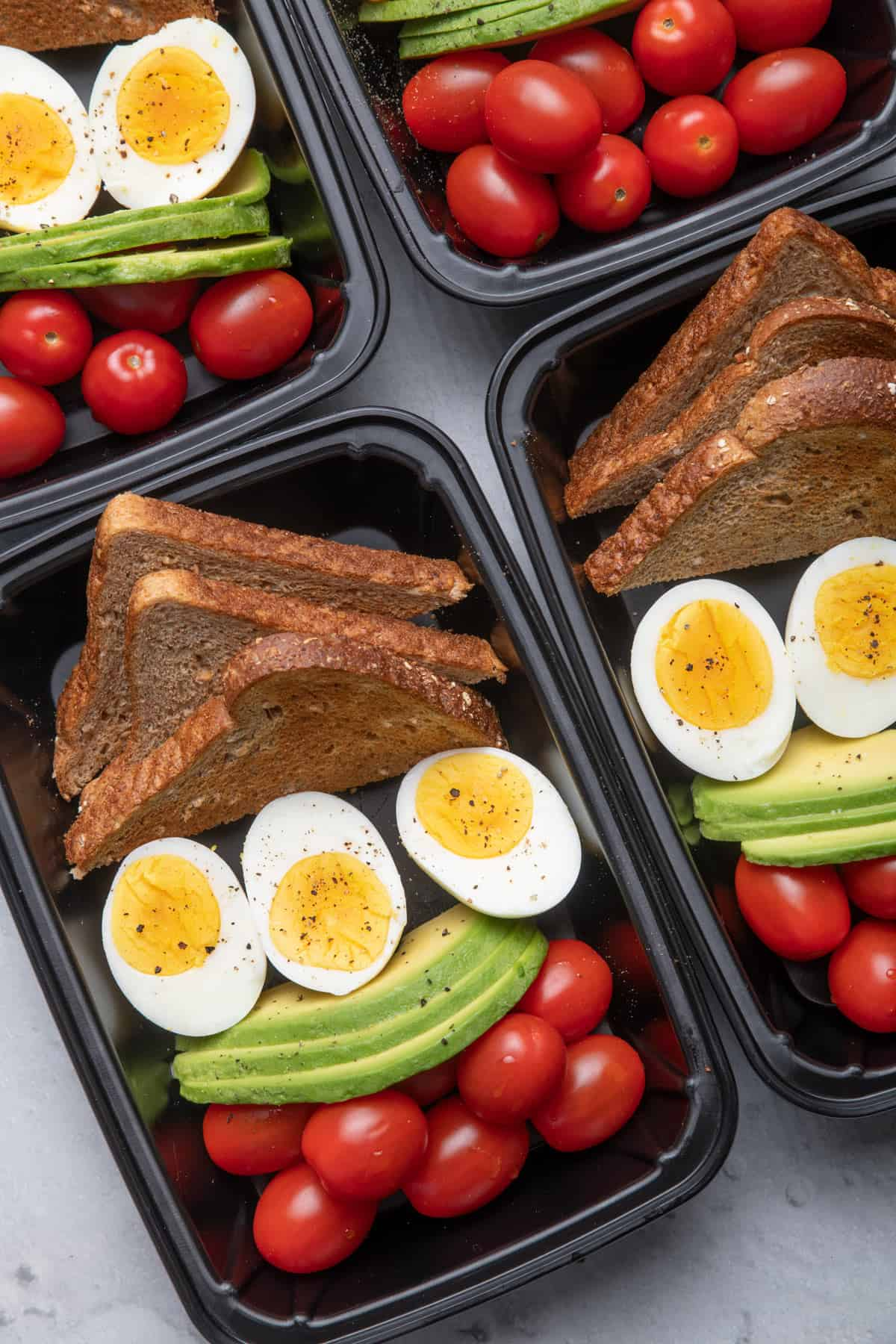 Meal prep containers with eggs, avocado, tomato and toast