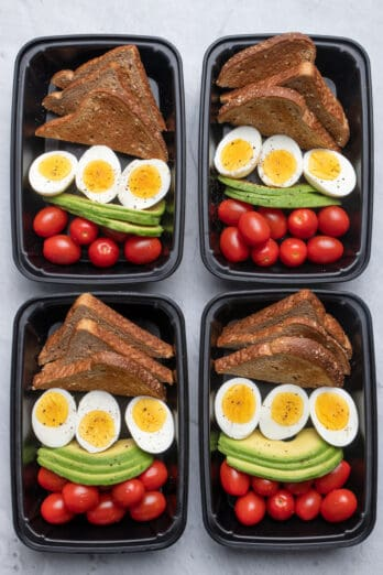 4 meal prep containers with the avocado, egg, toast and tomatoes