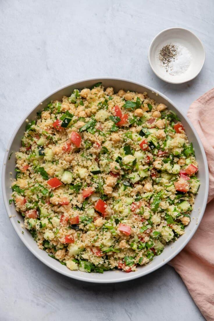 Large bowl of bulgur salad with salt and pepper in pinch bowl to it