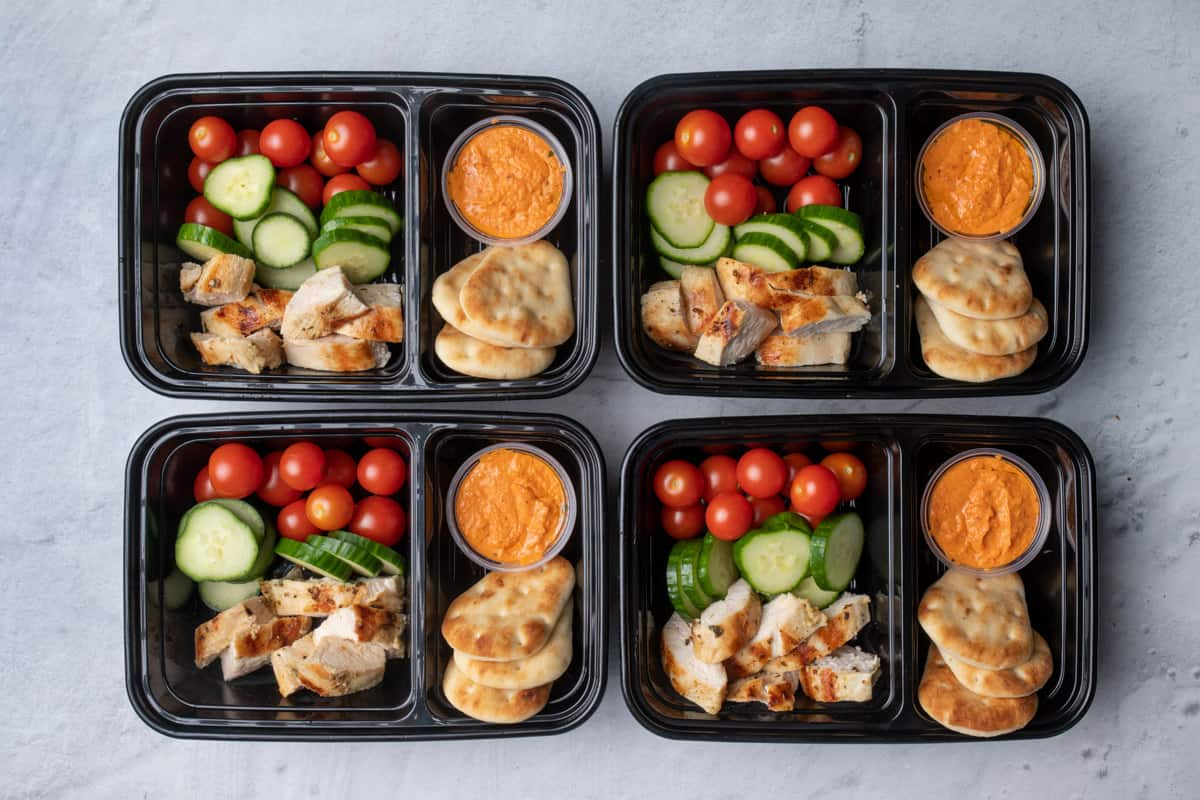 Grilled chicken and hummus meal prep containers with vegetables and naan bread