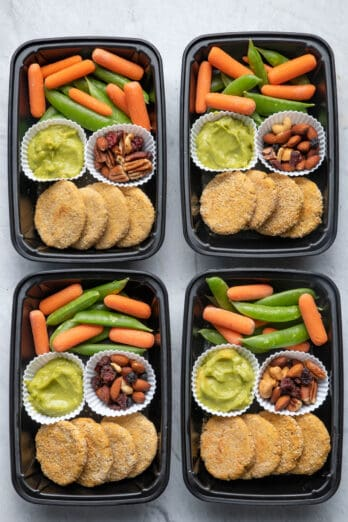 4 meal prep containers with the chickpea bites and avocado dip along with veggies and trail mix