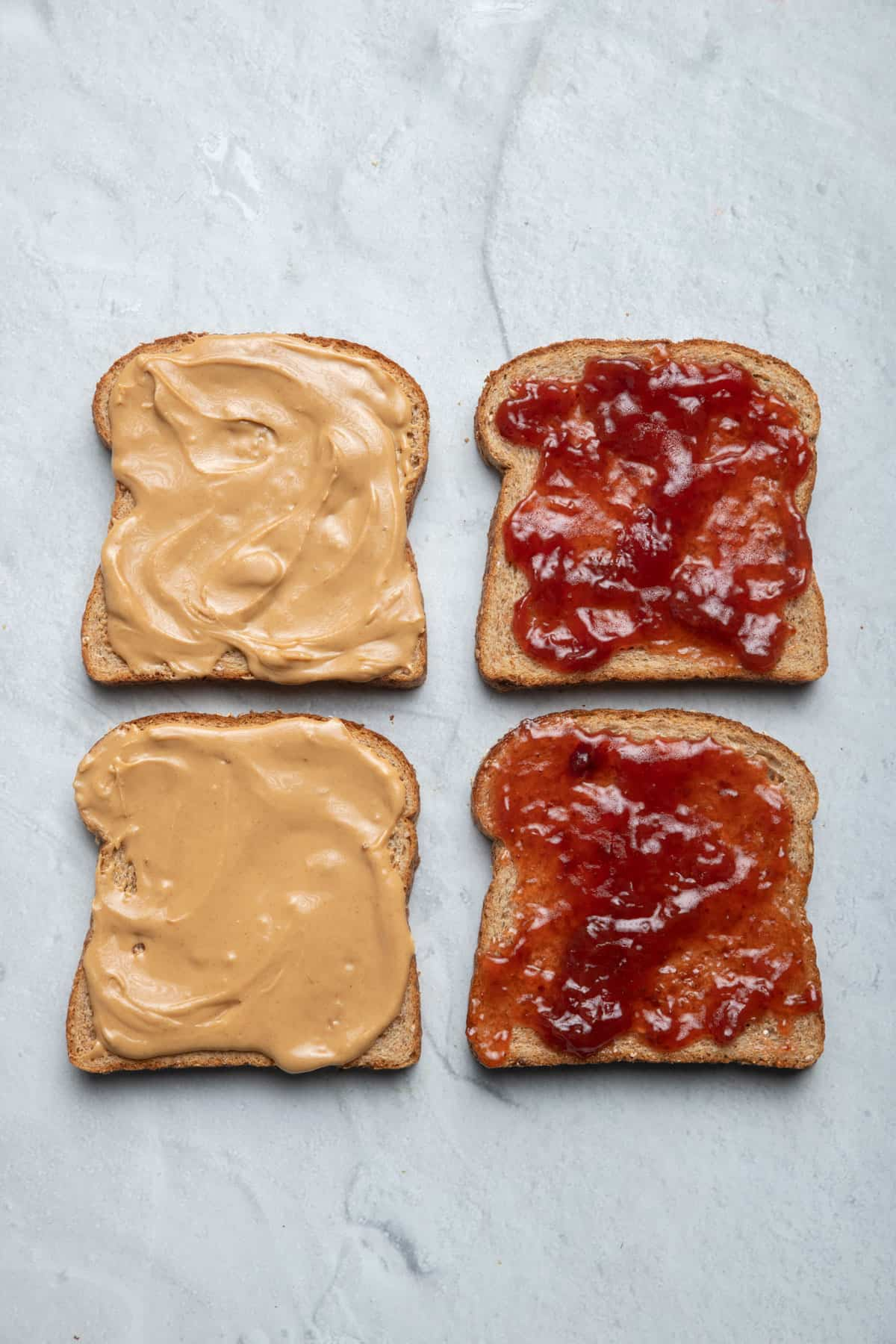 Four slices of bread with peanut butter and jelly on them