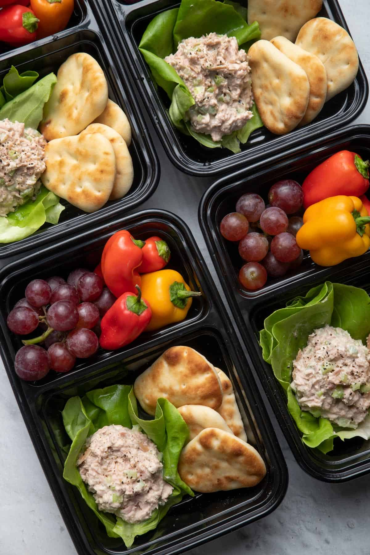 Tuna salad meal prep containers with vegetables and fruit