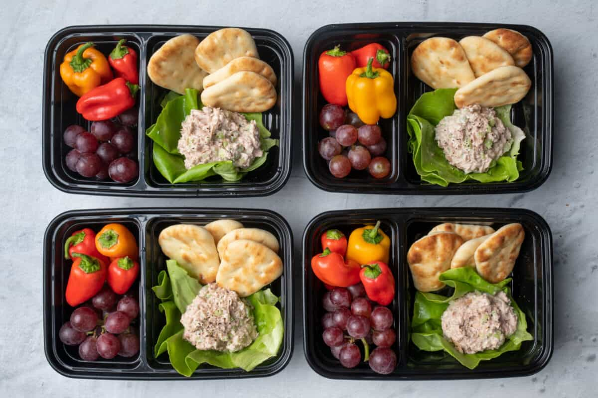 4 tuna salad meal prep containers with pita, peppers and graps