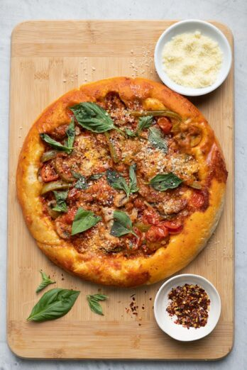 Upside down pizza on cutting board with parmesan cheese, crushed red pepper and basil