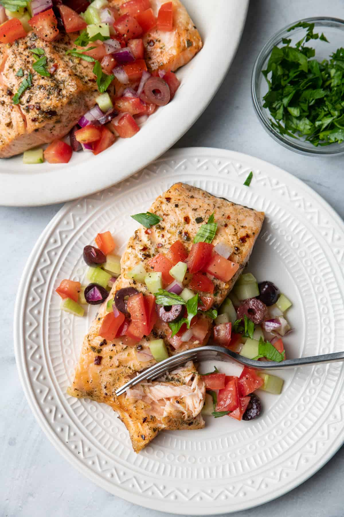 Plate of salmon cooked in air fryer, topped with greek salad