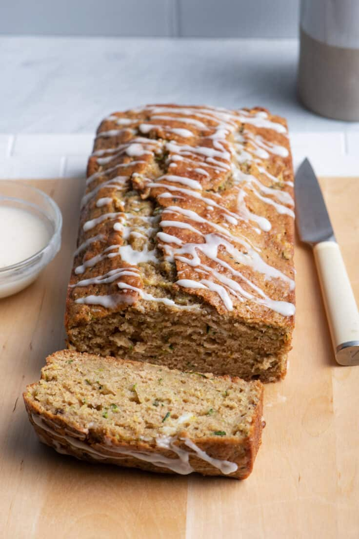 Lemon zucchini bread drizzled with glaze on cutting board