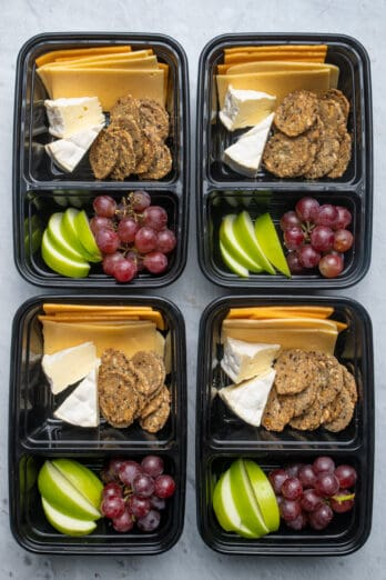 Meal prep containers with cheese, fruit and crackers