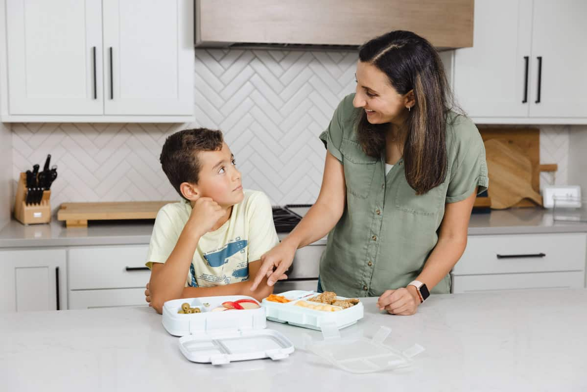 Yumna with son (Adam) pointing at lunchboxes