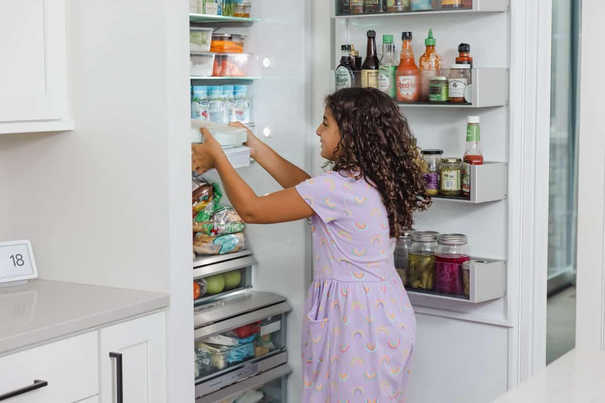 Carine putting away lunchbox in fridge