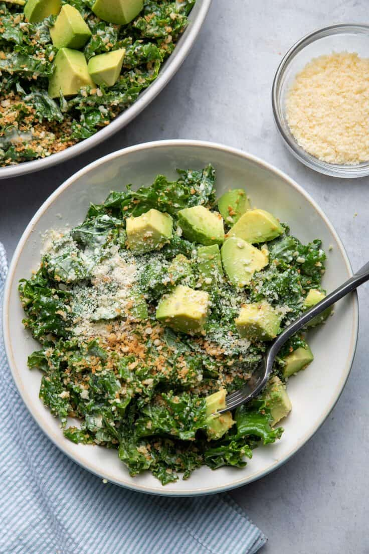 Kale Caesar Salad in a bowl served with avocados on top