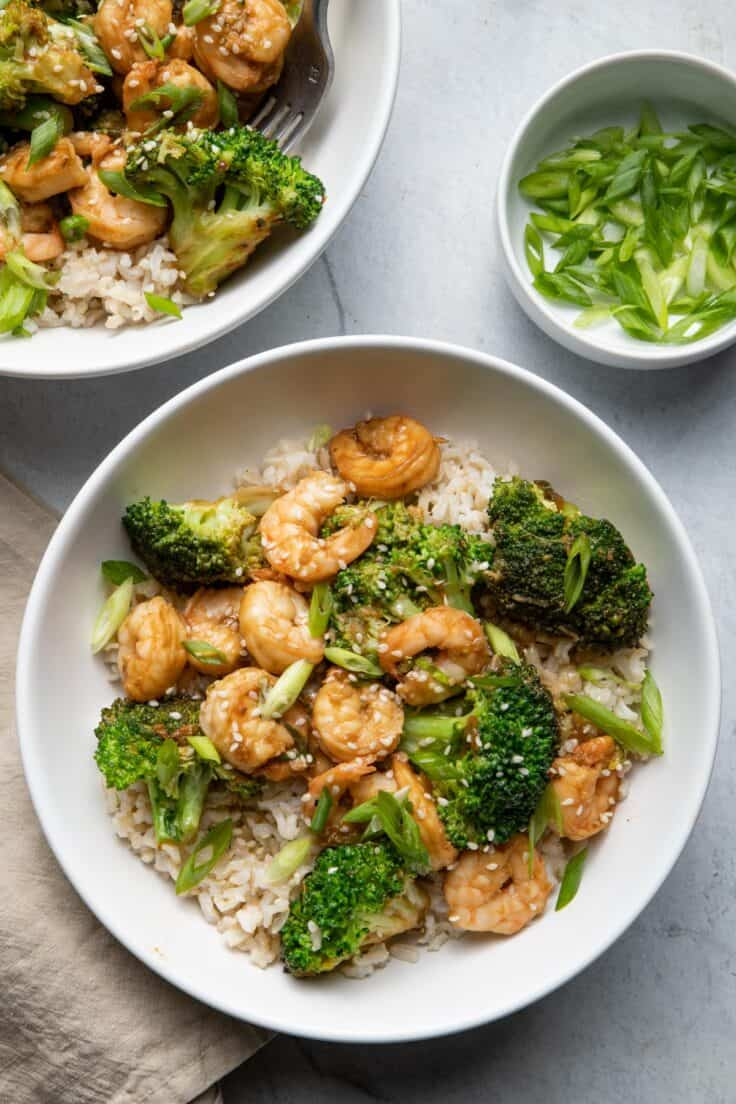 Shrimp and broccoli stir fry in bowls over brown rice