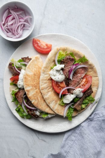 Two steak gyros on a plate with toppings