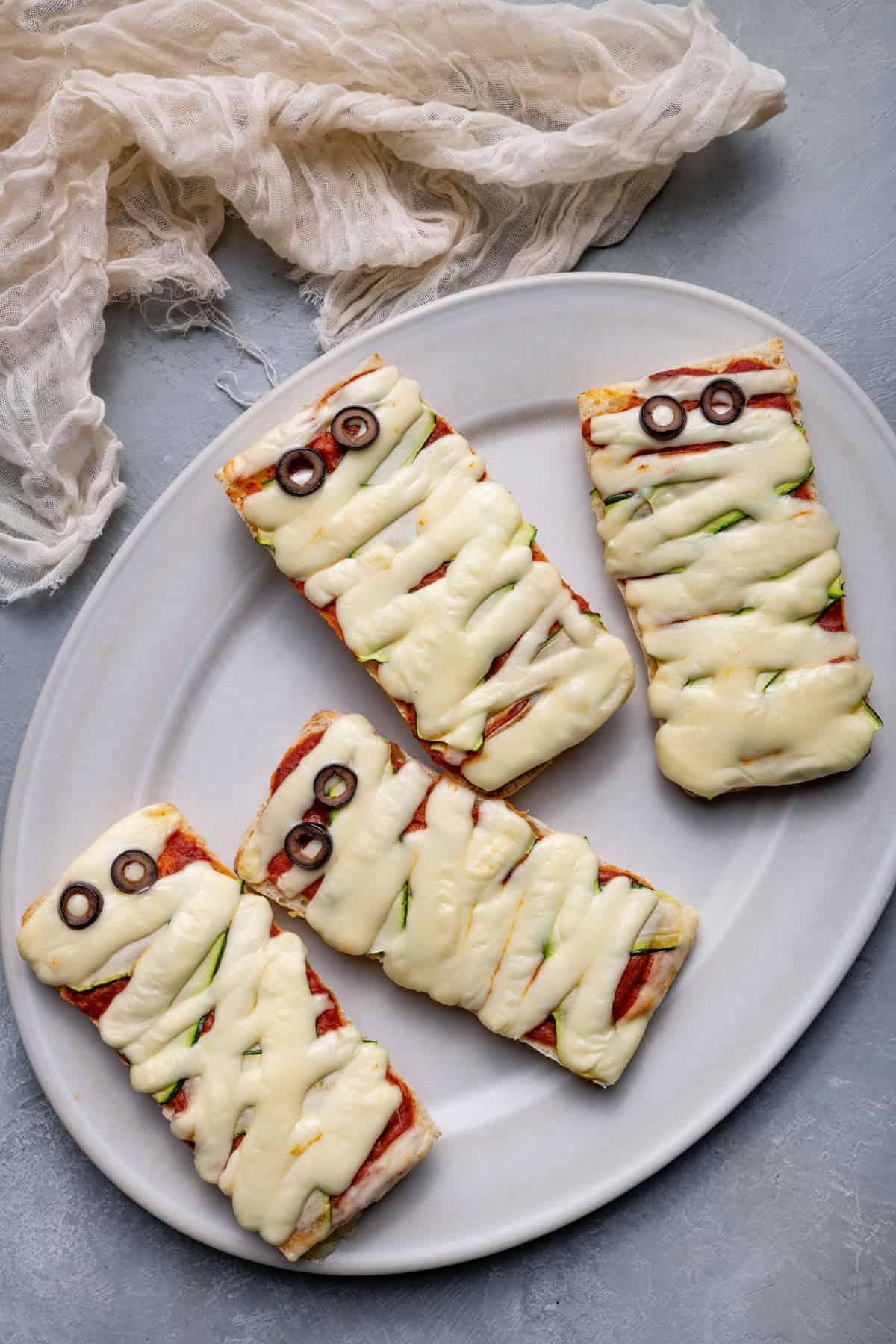 Mummy pizzas on a platter